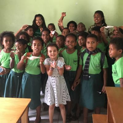 A mother and her daughter take a group photo with the students they worked with in Fiji